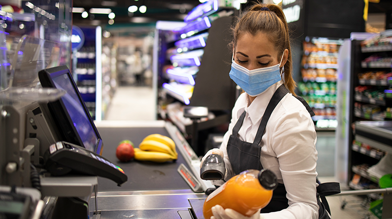 female grocery cashier with mask scanning item