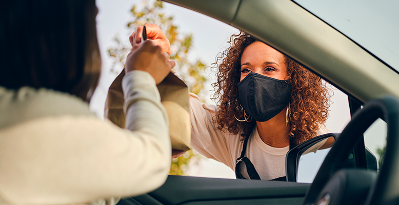 female employee with mask handing customer in car their order